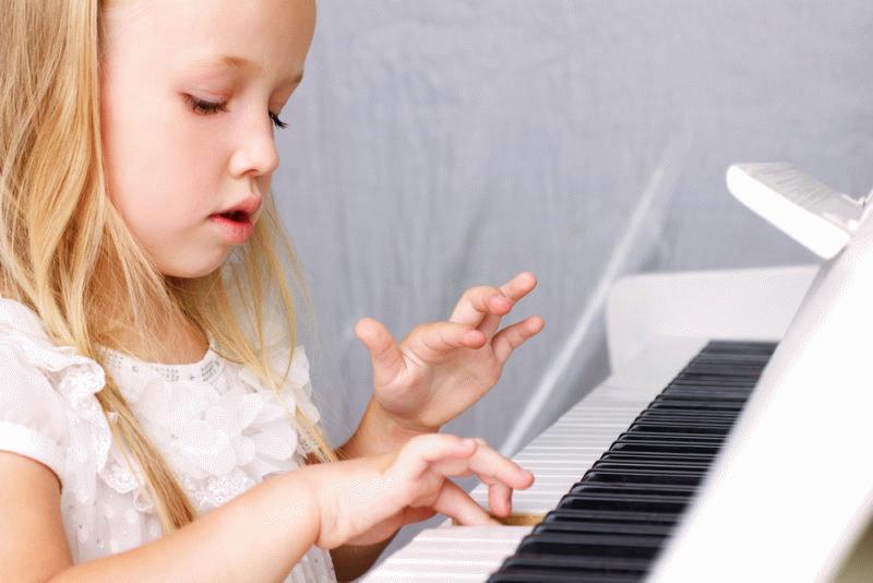 Ребенок играет на фортепиано.